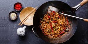 Immagine con wok, ciotole e bacchette